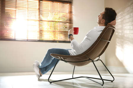 Young man with cup of drink relaxing near window at home. Space for text