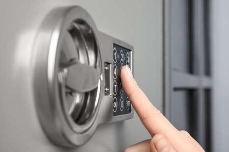 Woman opening steel safe with electronic lock, closeup Standard-Bild