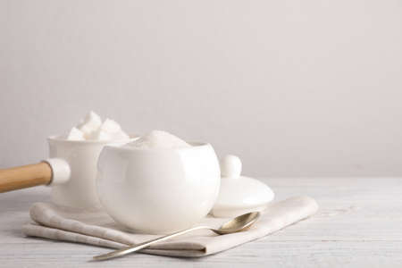 Dishware with sugar on white wooden table. Space for text