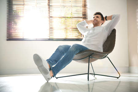 Young man relaxing near window at home. Space for text