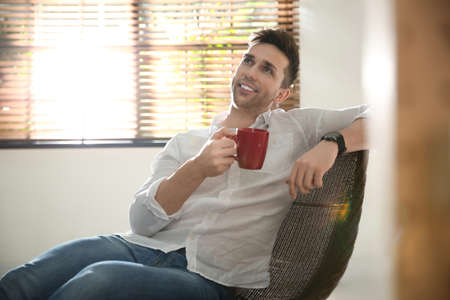 Young man with cup of drink relaxing near window at home