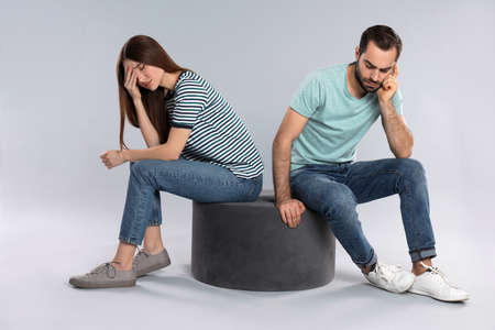 Couple with relationship problems on light grey background