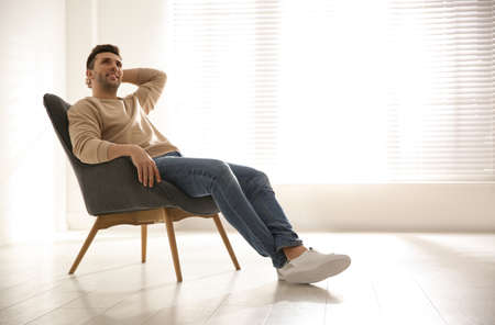 Young man relaxing in armchair near window at home. Space for text
