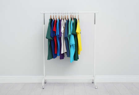 Rack with stylish colorful t-shirts in room