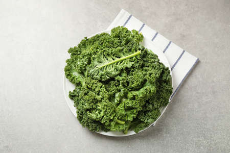 Fresh kale leaves on grey table, flat lay