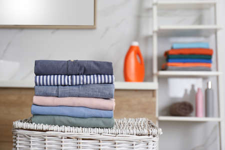 Stack of fresh laundry on basket in bathroom