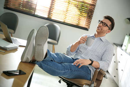 Young man with cup of drink relaxing at workplace Zdjęcie Seryjne