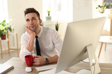 Young businessman with cup of drink relaxing at table in office during break