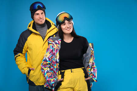 Couple wearing stylish winter sport clothes on light blue background