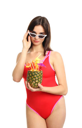 Beautiful young woman with exotic cocktail wearing swimsuit and sunglasses on white background