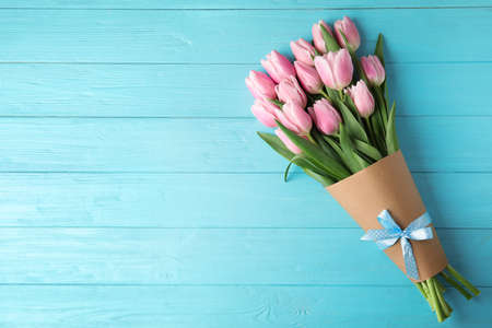 Beautiful pink spring tulips on light blue wooden background, top view. Space for text