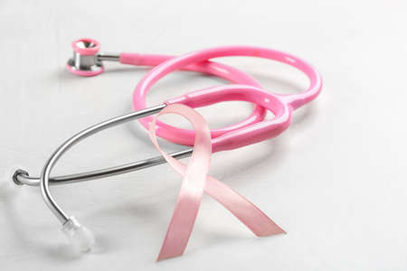 Pink ribbon and stethoscope on light grey stone background, closeup. Breast cancer concept
