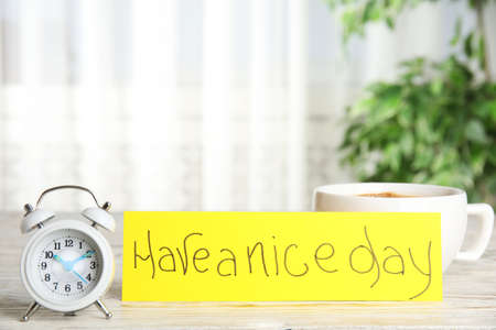 Delicious morning coffee, alarm clock and card with HAVE A NICE DAY wish on white wooden table indoors
