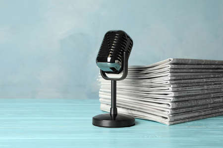 Newspapers and vintage microphone on light blue wooden table. Journalist's work
