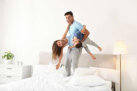 Padre feliz jugando con sus hijos en el dormitorio