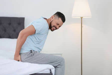 Man suffering from hemorrhoid on bed at home