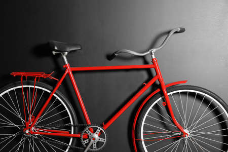 Red bicycle hanging on black wall, closeup