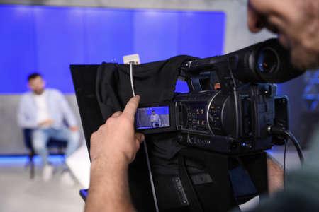 Professional video camera operator working in studio, closeup