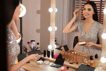 Beautiful young woman applying makeup near mirror in dressing room Stock Photo