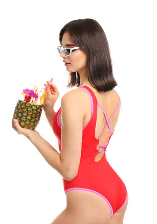 Beautiful young woman with exotic cocktail wearing swimsuit and sunglasses on white background Foto de archivo