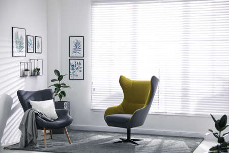 Comfortable armchairs near window in light room
