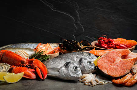 Fresh fish and different seafood on grey table