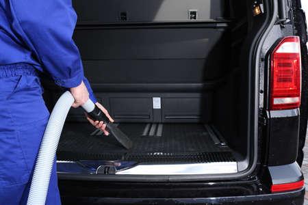 Worker using vacuum cleaner in automobile trunk at car wash, closeup 版權商用圖片