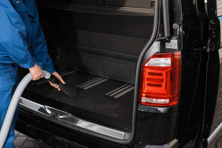 Worker using vacuum cleaner in automobile trunk at car wash, closeup