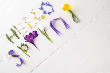 Words HELLO SPRING made of fresh flowers on white wooden table, flat lay. Space for text