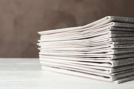 Stack of newspapers on white wooden table. Journalists work