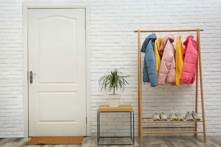 Wooden rack with stylish warm jackets in hallway Stock Photo