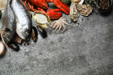 Fresh fish and different seafood on grey table, flat lay. Space for text