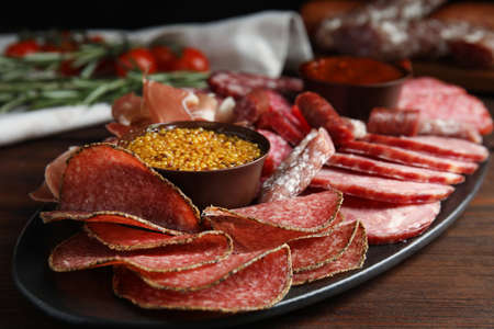 Different types of sausages with mustard served on wooden table, closeup