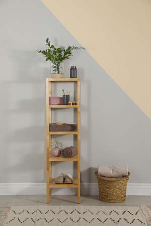 Shelving unit with toiletries near light wall indoors. Bathroom interior element