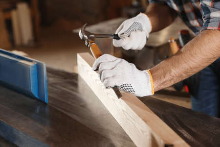 Professional carpenter working with wooden plank in workshop, closeup