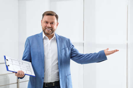 Male real estate agent with clipboard in new apartment