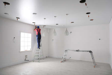 Worker installing stretch ceiling in empty room