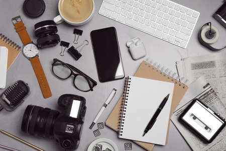 Flat lay composition with equipment for journalist on grey stone table