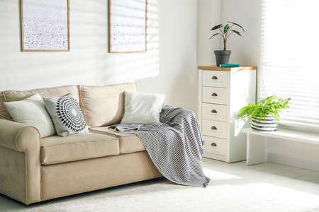 Stylish decorative pillows on beige couch indoors Zdjęcie Seryjne