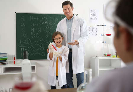 Teacher with pupil at chemistry lesson in classroom Stock Photo