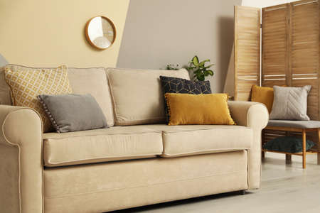 Modern comfortable sofa with pillows indoors. Stylish room interior