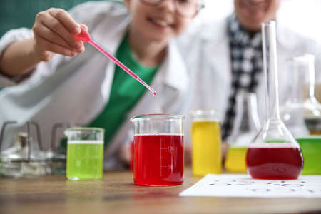 Teacher with pupil making experiment at table in chemistry class, focus on flask Stock Photo