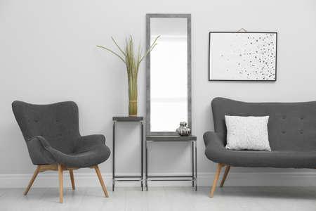 Modern mirror near white wall in stylish living room