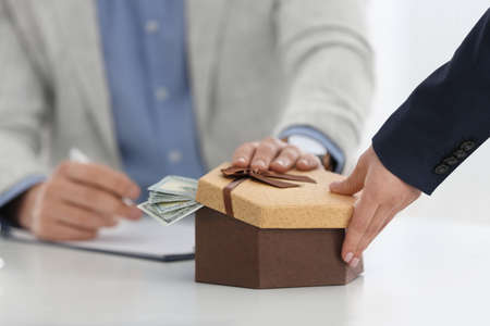 Woman giving bribe to man at table in office, closeup Stock Photo