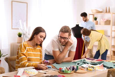 Diseñadores de moda creando ropa nueva en estudio.