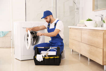 Professional plumber repairing washing machine in bathroom Reklamní fotografie