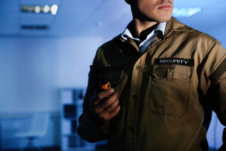 Professional security guard with portable radio set in dark room, closeup Stock Photo