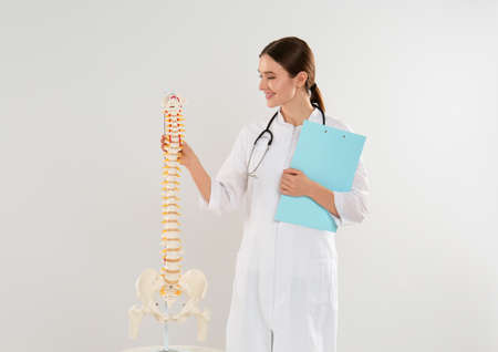 Female orthopedist with human spine model against light background