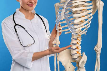 Female orthopedist with human skeleton model on blue background, closeup