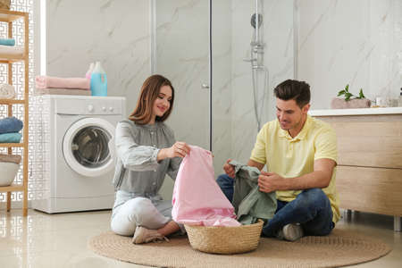 Happy couple with clean laundry in bathroom Foto de archivo - 140897960